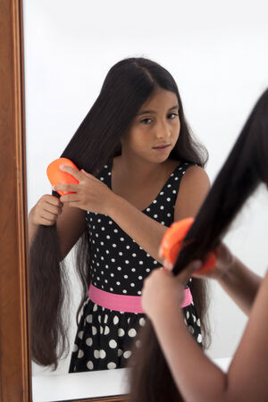 eleven: Young teenage girl brushing her hair in the mirror