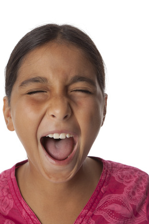 Young teenage girl screaming loud on white background