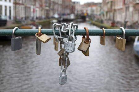 Closed bicycle locks hanging on the bridge above the canal photo