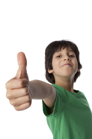Happy eight year old boy sticks his thumb up on white background