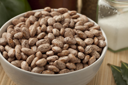 Bowl with pinto beans on the table photo