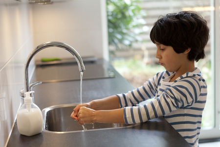 Eight year old boy washing hands in the kitchen