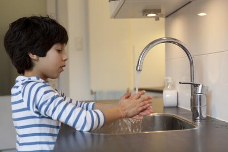 lavandose las manos: Ocho años de edad lavado manos muchacho en la cocina