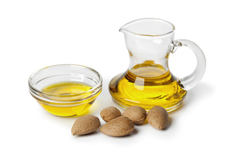 Almond oil and almonds on white background