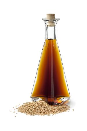 ajonjol�: El aceite de s�samo y semillas de s�samo tostadas en el fondo blanco