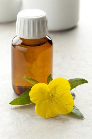 Fles met teunisbloemolie en verse bloemen