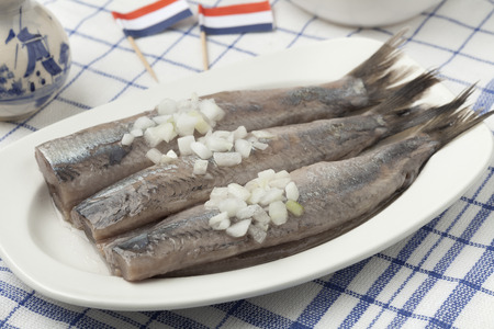 Dutch raw herring with onions on a dish