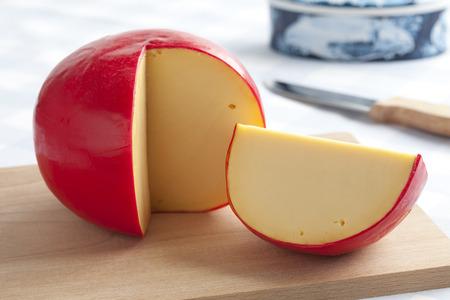 Edammer kaas en een stuk op een snijplank