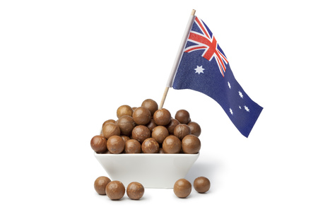 nutricion: Bowl with macadamia nuts and the australian flag on white background Stock Photo