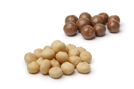 nutricion: Peeled and unpeeled macadamia  nuts  on white background