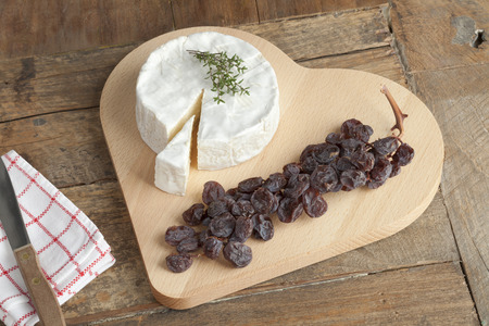 cheese board: Camembert cheese with a twig of muscat raisins on a heart shaped cheese board