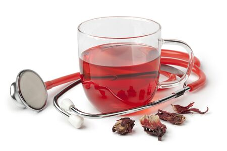 alternative medicine: Cup of hibiscus tea and stethoscope on white background