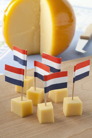edam: Yellow Edam cheese blocks with Dutch flags as a snack Stock Photo