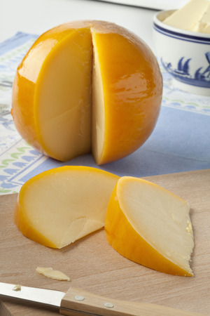 edam: Whole yellow round Edam cheese with slices on a cutting board