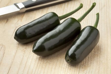 jalapeno: Three fresh green Jalapeno chili peppers on a cutting board Stock Photo