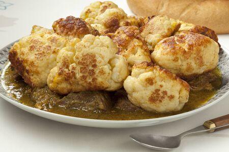 coliflor: Coliflor profunda tradicional marroquí frito con carne y salsa en un plato
