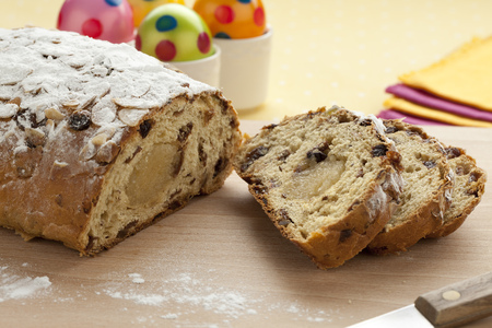 Traditional whole dutch easter bread covered with sugar and easter eggs on the background