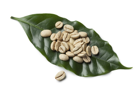 unroasted: Heap of Indian Malabar green unroasted coffee beans on a coffee plant leave on white background Stock Photo
