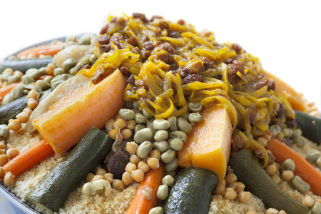 couscous: Festive Moroccan couscous with onions and raisins on a dish close up Stock Photo
