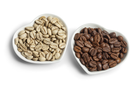unroasted: Heartshaped bowls with Indian Malabar green unroasted and brown roasted coffee beans on white background Stock Photo
