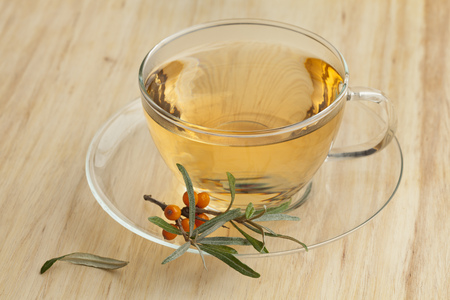 argousier: Cup of sea buckthorn tea with a twig of common sea-buckthorn Banque d'images