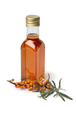 Bottle Sea buckthorn oil  with a twig of common sea-buckthorn on white background