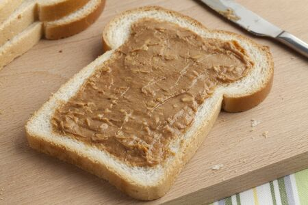 sandwich spread: Slice of white bread with peanut butteron a wooden cutting board