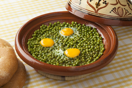 sunny side up: Moroccan tajine with green peas and sunny side up eggs Stock Photo