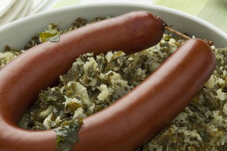 smoked sausage: Traditional dutch dish with stewed curly kale and smoked sausage close up Stock Photo