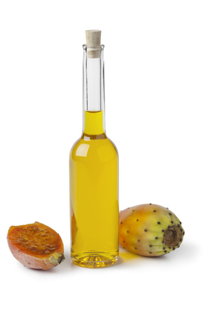 Bottle of prickly pear seed oil and prickly pears on white background