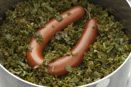 sausage pot: Cooking pot with cooked curlly kale and smoked sausage