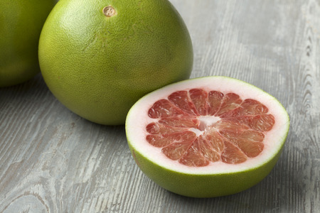 citrus maxima: Fresh red whole and half pomelo fruit