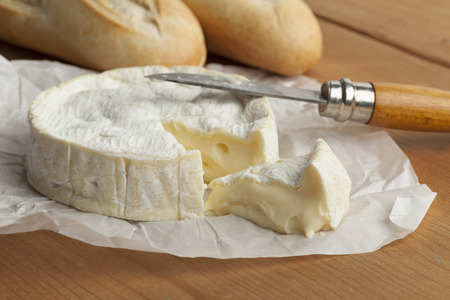 Ripe French camembert cheese and a slice Фото со стока - 48048795