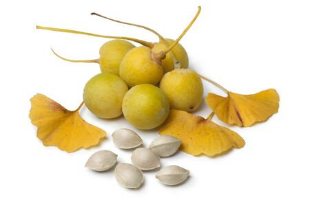 Ripe yellow Ginkgo biloba fruit, nuts and leaves on white background Stockfoto