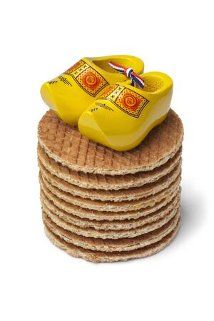 wooden shoes: Fresh baked Dutch syrup waffles with yellow mini wooden shoes on white background