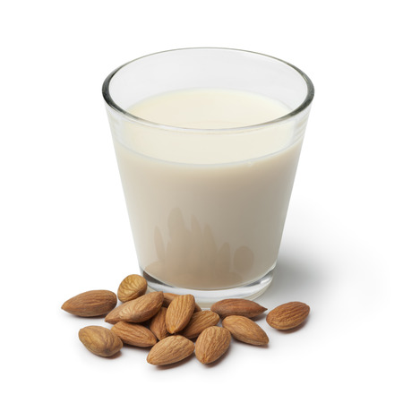 Glas van Almond melk met een hoop van amandelen op een witte achtergrond