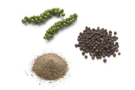 pepe nero: Fresh drupe pepe verde, pepe nero e polvere su sfondo bianco