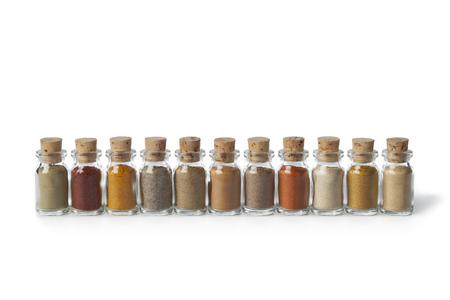 yerbas: Fila de las botellas de vidrio con diferentes hierbas en polvo en el fondo blanco