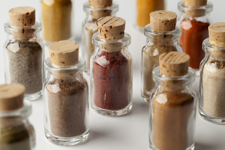variety: Glass bottles with different powder herbs on white background