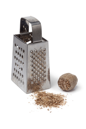 ground: Ground nutmeg kernel and grater on white background