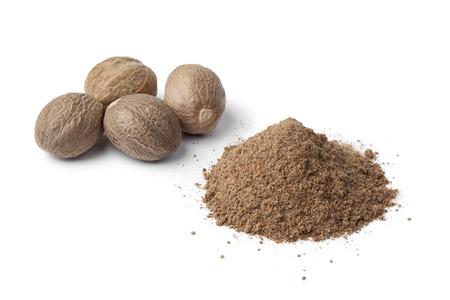 Heap of ground Nutmeg powder and seeds on white background