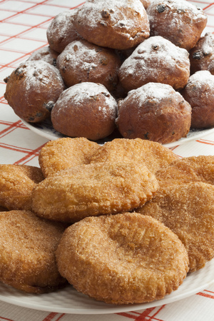 Heap of sugared fried fritters called oliebollen and appelflappen on a dish