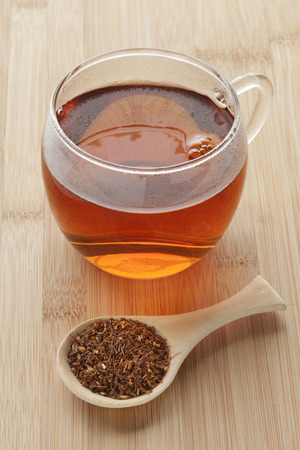 red bush tea: Cup with South African Rooibos tea and a spoonful dried tea