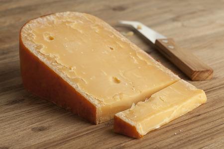 tabla de quesos: Pedazo de tres a�os de edad queso Gouda en una tabla de quesos