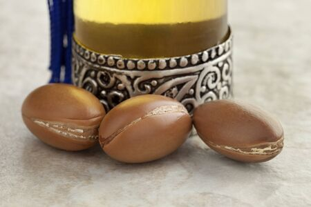 argan: Bottle with moroccan argan oil and nuts close up