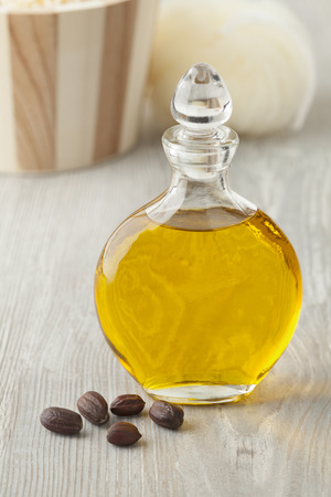 Bottle of cosmetic Jojoba oil and seeds