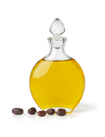 Botle of Jojoba oil and seeds on white background