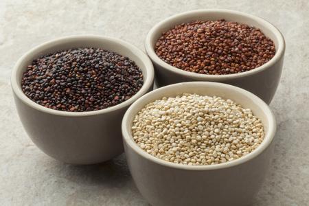 Schüsseln mit roh rot, weiß und schwarz Quinoa