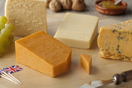 tabla de quesos:  Pieces of traditional english cheese on a cheeseboard