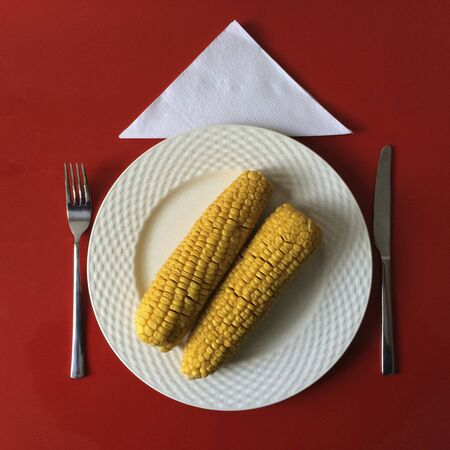 red cooked: Two cooked corn on the cob on a plate on a red table